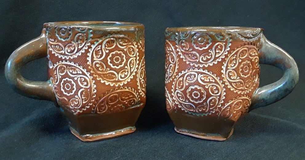 Two small brown mugs stamped with designs in grey.