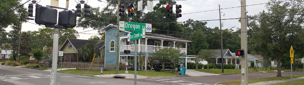 A photo of City street sign for Fern Creek and Oregon with the intersection and blue house in the background.