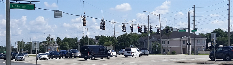 A photo of vehicles turning left from Raleigh Street onto Kirkman Road, traffic signals and street sign visible.
