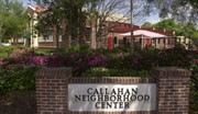 Exterior of the Callahan Neighborhood Center, a brick building with trees and flowers out front. In the foreground is the center's sign.